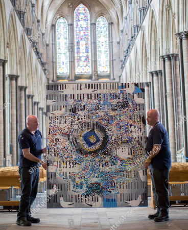 Stock Image of Salisbury Cathedral Caretakers Steve and Tony Marshall as they  move The Miracle of Song 2014 into place.
