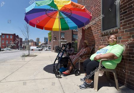 Resident Sharone Henderson, right, sits with neighbors Timothy Taylor, left, and Grace Homer, second from left, at the Perkins Homes public housing development in Baltimore on