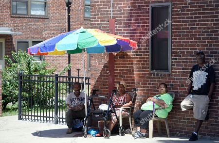 Resident Sharone Henderson, third from right, sits with neighbors Timothy Taylor, left, and Grace Homer, second from left, at the Perkins Homes public housing development in Baltimore on