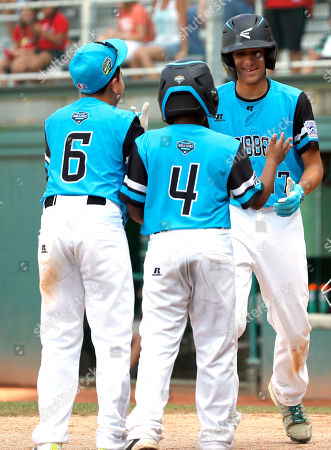 Puerto Rico's Carlos De Jesus (17) is greeted by teammates Gabriel Rivera (6) and Leonel Gomez (4) after hitting a home run off of Canada's pitcher Cole Balkovec in the sixth inning of an elimination baseball game in International pool play at the Little League World Series tournament in South Williamsport, Pa., . Puerto Rico won the game 9-4, eliminating Canada