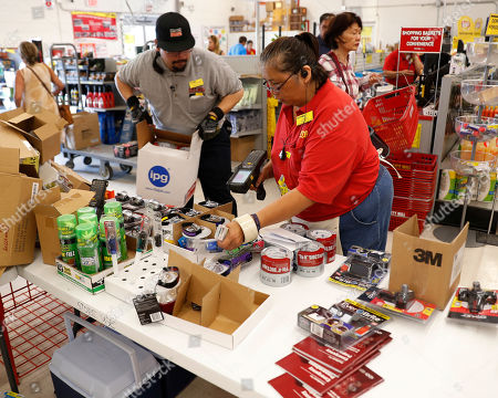 Stock Photo of City Mill hardware store sales associates Frank Miller Gascon, left, Lisa Lavilla, fill a table up with duck tape, flashlights, and other hurricane supplies, in Honolulu. Gascon said he's been filling the table up every ten minutes as supplies are being swept up by shoppers who are preparing for the approaching Hurricane Lane. Hurricane Lane has weakened as it approaches Hawaii but was still expected to pack a wallop, forecasters said Wednesday