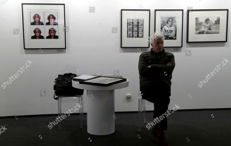 A man sits in front of several images of the British singer John Lennon, taken by the US photographer Bob Gruen, during the opening of the Lima Photo 2018 fair, in Lima, Peru, 22 August 2018.The Lima Photo 2018 fair, the largest exhibition in the photography market in Peru, will exhibit artistic and visual proposals from 20 galleries from seven countries, in a privileged area of 2,500 square meters in the Miraflores district.