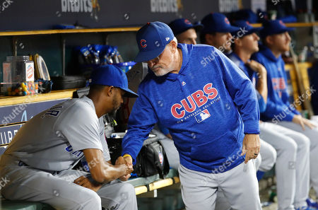 Chicago Cubs manager Joe Maddon, right, shakes hands with Chicago Cubs relief pitcher Carl Edwards Jr. in the dugout in the eighth inning of a baseball game in Detroit