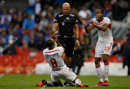 Toluca's William Da Silva, 8, and Luis Quinones, right protest to referee Francisco Chacon during a national league soccer match against Cruz Azul at the Azteca Stadium in Mexico City