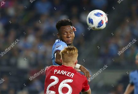Stock Photo of Rodney Wallace,Tim Parker. NYCFC midfielder Rodney Wallace, center, heads the ball away from New York Red Bulls defender Tim Parker during the second half of an MLS soccer match, in New York. The match ended in a 1-1 draw