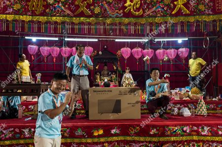 Organisers give away prizes during a raffles at a banquet and Chiu Chow opera performance in the New Territories in Hong Kong, China, 22 August 2018 (issued 23 August 2018). Around 1.2 million people originating from Chiu Chow (Chaozhou) in China's Guangdong province live in Hong Kong. During the Hungry Ghost Festival, they organise their own Yu Lan Ghost Festival, which includes opera performances for ghosts in need of a bit of entertaining. While the festival's origins are not unlike those of Halloween in Europe, it is also intrinsically linked to the Chinese practice of ancestor worship.