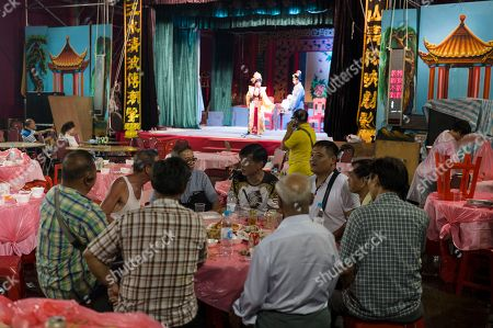 Guests attend a banquet during a Chiu Chow opera performance in the New Territories in Hong Kong, China, 22 August 2018 (issued 23 August 2018). Around 1.2 million people originating from Chiu Chow (Chaozhou) in China's Guangdong province live in Hong Kong. During the Hungry Ghost Festival, they organise their own Yu Lan Ghost Festival, which includes opera performances for ghosts in need of a bit of entertaining. While the festival's origins are not unlike those of Halloween in Europe, it is also intrinsically linked to the Chinese practice of ancestor worship.