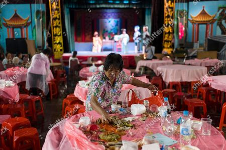 A woman cleans up a table after a banquet and a Chiu Chow opera performance in the New Territories in Hong Kong, China, 22 August 2018 (issued 23 August 2018). Around 1.2 million people originating from Chiu Chow (Chaozhou) in China's Guangdong province live in Hong Kong. During the Hungry Ghost Festival, they organise their own Yu Lan Ghost Festival, which includes opera performances for ghosts in need of a bit of entertaining. While the festival's origins are not unlike those of Halloween in Europe, it is also intrinsically linked to the Chinese practice of ancestor worship.