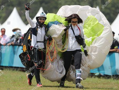 South Korean Da Gyeom Lee (L) celebrates while accompanied by her teammate Woo Young Jang (R) after winning the silver medal in the women's Paragliding individual accuracy competition of the 18th Asian Games Jakarta-Palembang 2018 in Jakarta, Indonesia, 23 August 2018. The Asian Games will take place from 18 August until 02 September 2018 in Jakarta and Palembang