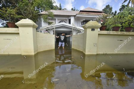 A man closes the gate of his house submerged in flood waters on in the outskirts of Alappuzha, India.