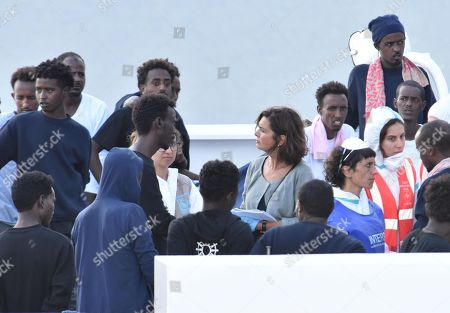 Former Chamber of Deputies' President Laura Boldrini (C) talks with some migrants as they wait to disembark from Italian Coast Guard ship Diciotti in the port of Catania, Italy, 23 August 2018. The vessel had arrived between Sunday and Monday with 177 migrants on board, but the Italian Interior Ministry denied them to disembark, calling EU member states to find a solution on how to distribute them. Last night, 27 unaccompanied minors were let off from the ship, assisted by Red Cross, UNHCR and Save the Children.