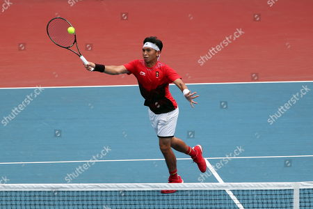 Christopher Benjamin Rungkat of Indonesia in action against Erina Hayasi and Kaito Uesugi of Japan (unseen) during the Tennis Mixed Doubles semifinal at the Asian Games 2018 in Palembang, Indonesia, 24 August 2018.