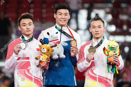 (L-R) Silver medalist Wei Sun of China, gold medalist Chia Hung Tang of Taiwan and bronze medalist Routeng Xiao of China pose on the podium during the medal ceremony for the Men's Horizontal Bar during the artistic gymnastics men's individual finals at the Asian Games 2018 in Jakarta, Indonesia, 24 August 2018.