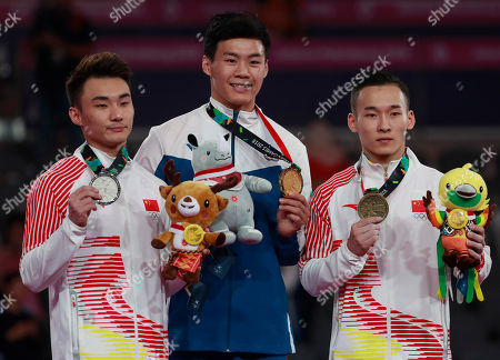 From left to right, silver medalist Sun Wei of China, gold medalist Tang Chia Hung of Taiwan, and bronze Xiau Ruoteng of China celebrate on the podium during the victory ceremony for high bar apparatus gymnastics competition at the 18th Asian Games in Jakarta, Indonesia