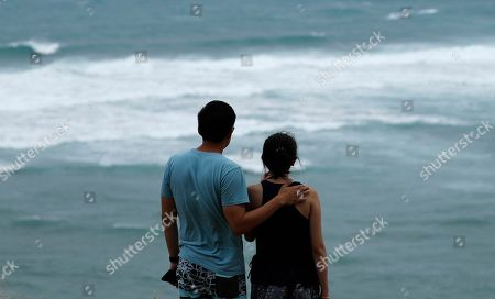 Dan Wong, left, and Cassie Tarleton watch waves crash along the coastline ahead of Lane, in Honolulu. As Lane approaches Oahu, large ocean swells have impacted local beaches and coastlines