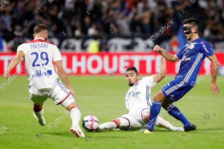 Lyon's Rafael Pereira Da Silva, center, passes the ball to Lucas Tousart, left, as they challenge with Strasbourg's Adrien Thomasson, right, during their French League One soccer match in Decines, near Lyon, central France