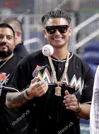 DJ Pauly D tosses a baseball before throwing a ceremonial pitch before a baseball game between the Miami Marlins and Atlanta Braves, in Miami