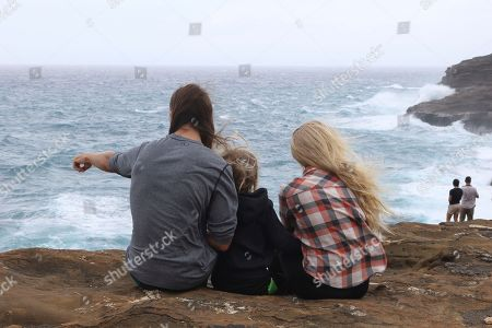 Michael Homyak, left, Kaity Sarina, right, and their son Tanner Homyak, all of Honolulu, sit along sea cliffs on the southeast shore of Oahu as Hurricane Lane approaches, near Honolulu