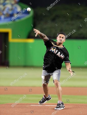 DJ Pauly D throws a ceremonial pitch before a baseball game between the Miami Marlins and the Atlanta Braves, in Miami