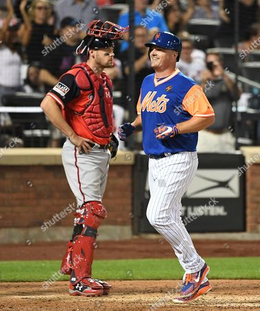 New York Mets' Jay Bruce reacts after he scores on his two-run home run as Washington Nationals catcher Jamie Burke stands near the plate during the eighth inning of a baseball game, in New York