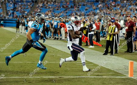Stock Photo of New England Patriots' Mike Gillislee (35) runs for a touchdown past Carolina Panthers' Richie Brown (49) during the second half of a preseason NFL football game in Charlotte, N.C