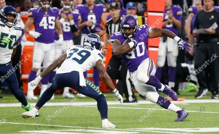 Minnesota Vikings fullback C.J. Ham (30) runs from Seattle Seahawks defensive back Dontae Johnson (39) during the first half of an NFL preseason football game, in Minneapolis