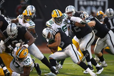 Green Bay Packers defensive end Muhammad Wilkerson (96) gets past a block by Oakland Raiders Oakland Raiders tackle Donald Penn (72) to tackle running back Doug Martin (28) during the first half of an NFL preseason football game in Oakland, Calif