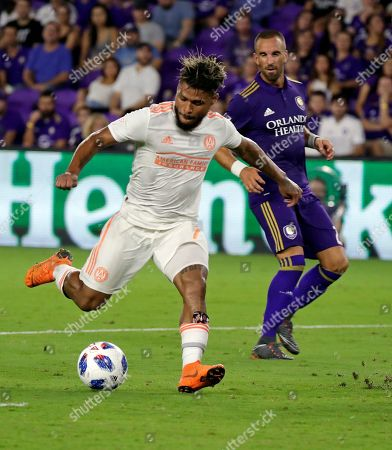 Atlanta United's Josef Martinez, left, takes a shot on goal past Orlando City's Jonathan Spector to score during the second half of an MLS soccer match, in Orlando, Fla. Martinez broke an MLS season goal record with his goal