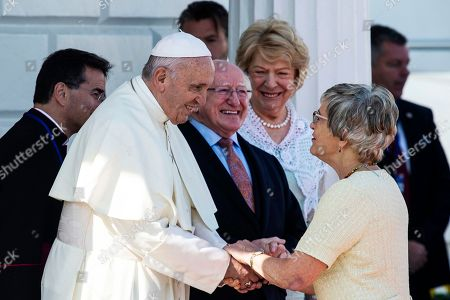 Pope Francis (2-L) shakes hands with Katherine Zappone, Minister of Minister for Children and Youth Affairs (R) as he is welcomed to the Aras an Uachtarain Presidential Residence in Dublin, Ireland, 25 August 2018.  The Pontiff  is visiting Ireland on 25 and 26 August 2018 to attend the World Meeting of Families (WMOF) 2018.