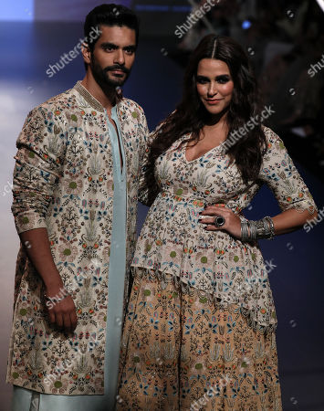 Stock Image of Bollywood actors Neha Dhupia (R) and Angad Bedi (L) presents a creation by Indian designers Payal Singhal during the Lakme Fashik Week (LFW) Winter/Festive 2018, in Mumbai, India, 25 August 2018. More than 90 designers are showcasing their collections at the event until 26 August