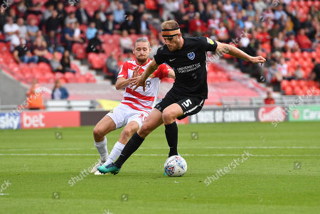 Portsmouth FC defender Matthew Clarke (5) sand Doncaster Rovers forward Alfie May (19) during the EFL Sky Bet League 1 match between Doncaster Rovers and Portsmouth at the Keepmoat Stadium, Doncaster.Photo by Ian Lyall