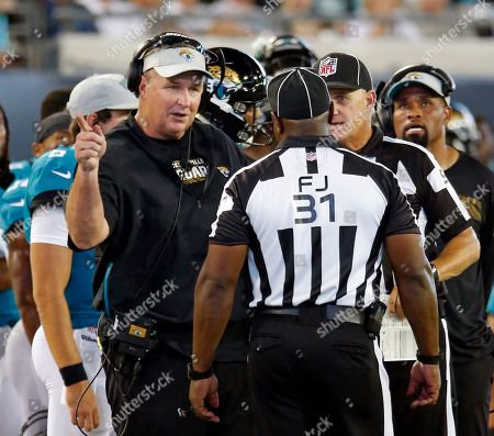 Jacksonville Jaguars head coach Doug Marrone, left, speaks with field judge Mearl Robinson (31) during the first half of an NFL preseason football game against the Atlanta Falcons, in Jacksonville, Fla