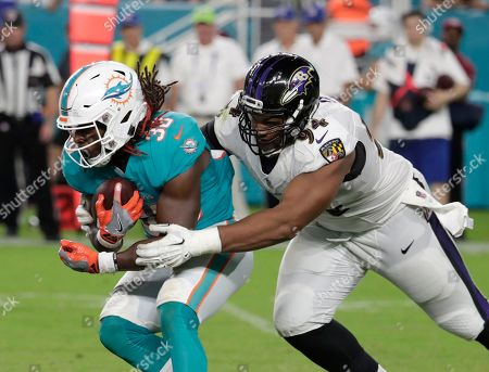 Baltimore Ravens defensive tackle Carl Davis (94) tackles Miami Dolphins running back Buddy Howell (38) during the second half of a preseason NFL game, in Miami Gardens, Fla. The Ravens defeated the Dolphins 27-10