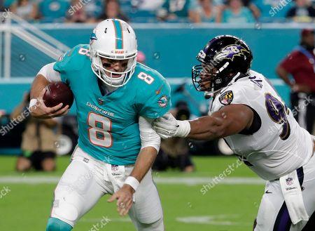 Brock Osweiler, Carl Davis. Miami Dolphins quarterback Brock Osweiler (8) scrambles under pressure from Baltimore Ravens defensive tackle Carl Davis (94) during the second half of a preseason NFL football game, in Miami Gardens, Fla