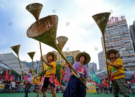 "Stock Picture of Participants try to catch rice in small orange color bags with baskets on sticks during the Ghost Grappling competition to mark the ""Hungry Ghost Festival"" at a downtown park in Hong Kong . Countless hungry and restless ghosts are roaming Hong Kong, and the world, to visit their living ancestors, at least according to Chinese convention. In traditional Chinese belief, the seventh month of the lunar year is reserved for the Hungry Ghost festival, or Yu Lan, a raucous celebration marked by feasts and music"