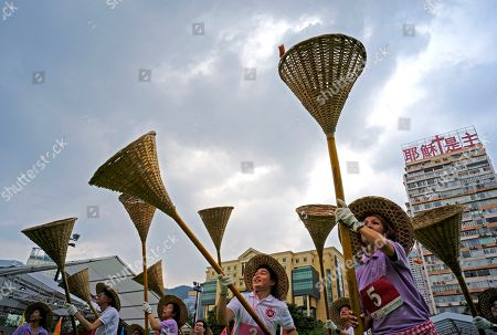 "Participants try to catch rice in small orange color bags with baskets on sticks during the Ghost Grappling competition to mark the ""Hungry Ghost Festival"" at a downtown park in Hong Kong . Countless hungry and restless ghosts are roaming Hong Kong, and the world, to visit their living ancestors, at least according to Chinese convention. In traditional Chinese belief, the seventh month of the lunar year is reserved for the Hungry Ghost festival, or Yu Lan, a raucous celebration marked by feasts and music"