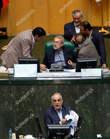 Iranian Economy and finance Minister Masoud Karbasian (bottom) speaks to defend himself as parliament speaker Ali Larijani (C, top) chats with lawmakers during an impeachment session at the Iranian Parliament in Tehran, Iran, 26 August 2018. Media reported that parliament sacked Karbasian as Minister of Economy and Finance as Iran is facing an economic crisis. The parliament impeached Economy Minister Masoud Karbasian and on the day voted to sack him.