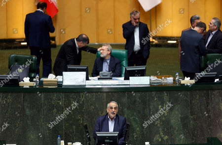 Iranian Economy and finance Minister Masoud Karbasian (bottom) speaks to defend himself as parliament speaker Ali Larijani (C, top) chats with a lawmaker during an impeachment session at the Iranian Parliament in Tehran, Iran, 26 August 2018. Media reported that parliament sacked Karbasian as Minister of Economy and Finance as Iran is facing an economic crisis. The parliament impeached Economy Minister Masoud Karbasian and on the day voted to sack him.