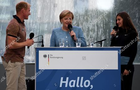 Stock Photo of German Chancellor Angela Merkel (C) speaks with German athletes Arthur Abele (L), Decathlon European Champion, and Gesa Felicitas Krause (R), 3000 m steeplechase European Champion,  during the 20th open day of the German Federal Government in Berlin, Germany, 26 August 2018. During the 20th open day of the Federal Government, visitors may have a look inside the Chancellery and most of the Government's ministries on 25 and 26 August 2018.