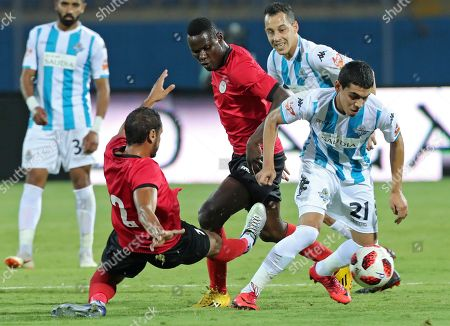 El Dakhlia players Mahmoud Shedid  (L) and Emmanuel Karbogi (C) in action against  Pyramids player Mohamed Hamdy (R) during the Egyptian league football match  between El Dakhlia and Pyramids in Cairo, Egypt, 26 Aygust 2018.