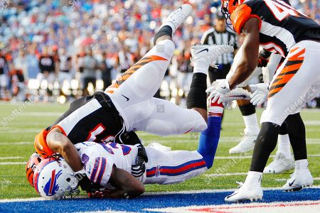 Buffalo Bills' Travaris Cadet (39) is tackled by Cincinnati Bengals' Brandon Bell (51) after crossing the goal line for a touchdown during the second half of a preseason NFL football game, in Orchard Park, N.Y