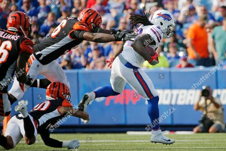 Buffalo Bills' Chris Ivory (33) runs away from Cincinnati Bengals' Carlos Dunlap (96) and Jessie Bates (30) during the first half of a preseason NFL football game, in Orchard Park, N.Y
