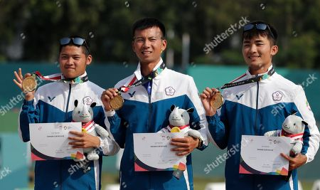 Winners Taiwan's Luo Weimin, Tang Chihchun and Wei Chunheng celebrate during the victory ceremony for the archery recurve men's team match at the 18th Asian Games in Jakarta, Indonesia