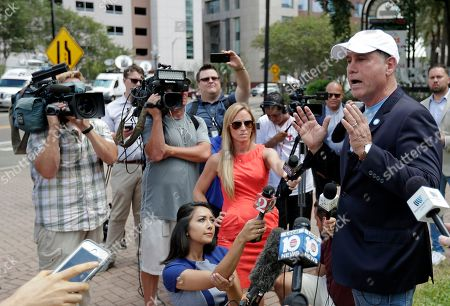 Florida Democratic gubernatorial candidate Philip Levine, right, talks to members of the media, near the scene of a mass shooting at The Jacksonville Landing in Jacksonville, Fla. A gunman opened fire Sunday at a video game tournament killing multiple people and then fatally shooting himself in a rampage that wounded several others