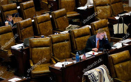 Rep. Joel Bomgar, R-Madison, right, takes advantage of the House recess to work at his desk, while waiting to be be called back to order, at the Capitol in Jackson, Miss., . Lawmakers are searching for money for roads and bridges and are seeking to pass a lottery bill that could help with the needed funding