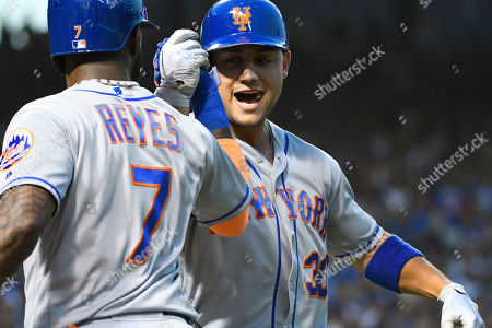 New York Mets' Michael Conforto (30) celebrates with Jose Reyes (7) after hitting a home run against the Chicago Cubs during the second inning of a baseball game on Monday, Aug, 27, 2018, in Chicago