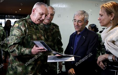 Commander of the Military Forces of Colombia General Alberto Jose Mejia (L) shows the digital version of the 'Genesis' report to Commander of the Colombian Army General Ricardo Gomez Nieto (C) and President of the Commission for the Clarification of Truth, Coexistence and Non-Repetition, priest Francisco De Roux (R) in Bogota, Colombia, 27 August 2018. The report 'Genesis' is a compilation of the Armed Forces of Colombia, about violations of the Revolutionary Armed Forces of Colombia (FARC) to Human Rights.
