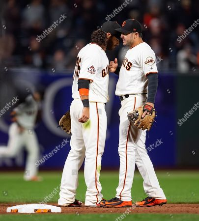 San Francisco Giants shortstop Brandon Crawford (35) talks with second baseman Chase d'Arnaud (2), after a 2-0 victory in a MLB game between the Arizona Diamondbacks and the San Francisco Giants at AT&T Park in San Francisco, California