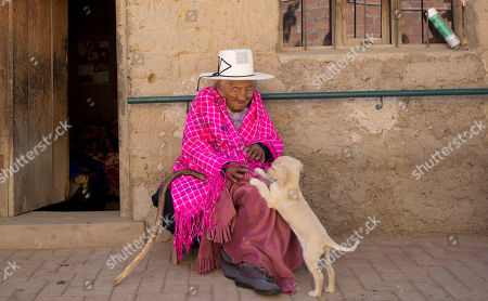 """117-year-old Julia Flores Colque plays with """"Chiquita,"""" one of the family pet dogs, while sitting outside her home in Sacaba, Bolivia. Flores Colque, who never married or had children, enjoys the company of her dogs, cats and rooster"""