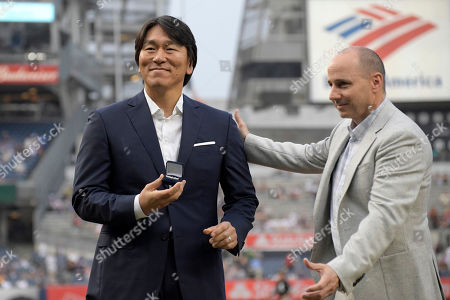 Former New York Yankees player Hideki Matsui was presented with a gift from Yankees general manager Brian Cashman, right, as Matsui was honored with a pregame ceremony celebrating his induction into the Japanese Baseball Hall of Fame earlier this year before a baseball game between the New York Yankees and the Chicago White Sox, at Yankee Stadium in New York